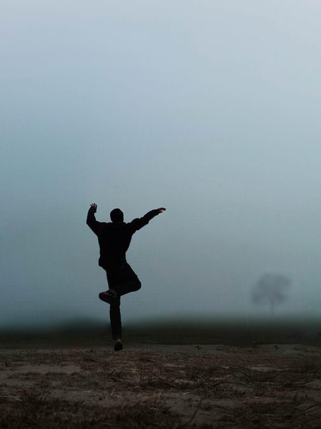 Eine Person tanzt auf einem nebeligen Feld.