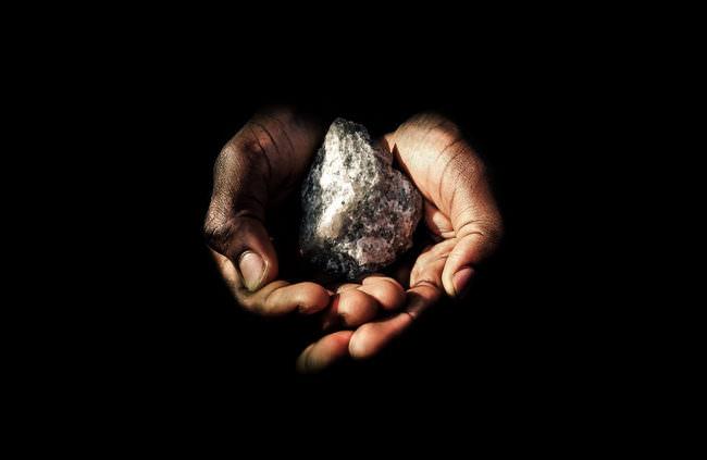 Zwei Hände halten einen Stein.