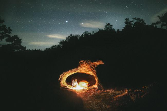 Zwei Personen stehen neben einem Lagerfeuer in einer Höhle unter Sternenhimmel