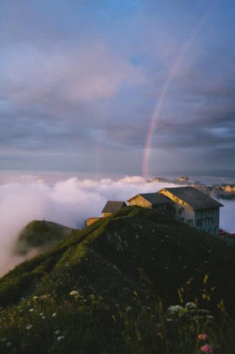 Ein Haus auf einem Berggipfel unter einem Regenbogen