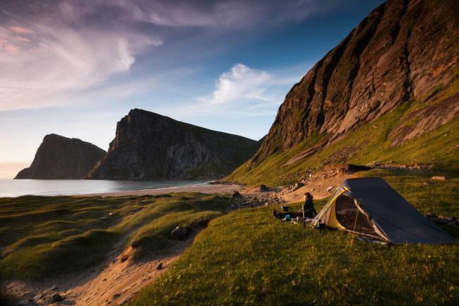 Ein Zelt steht an einer einsamen Küste im Grünen.