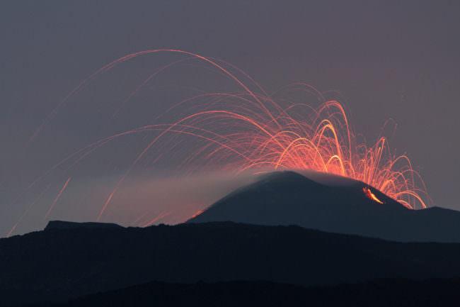 Rote Funken eines Vulkans über eines nächtlichen Landschaft.