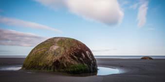 Ein kugelrunder moosiger Felsblock in einem Gewässer.