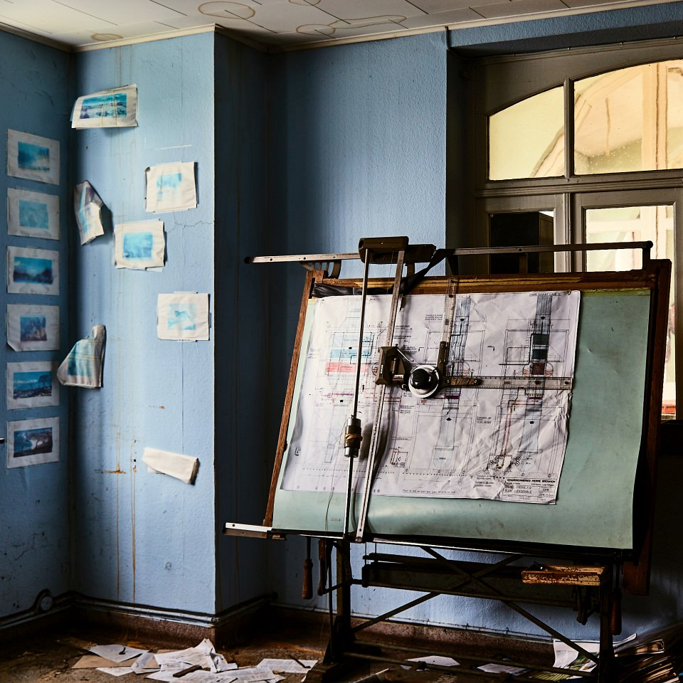 Arbeitsplatz mit Zeichnungstisch in einem Raum.