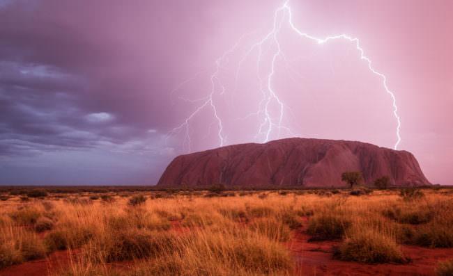 Blitzeinschlag in rosa Himmel über einer roten Landschaft.