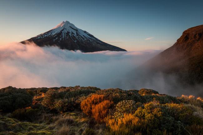 Ein von Nebelwolken umgebener Berg mit eisiger Spitze.