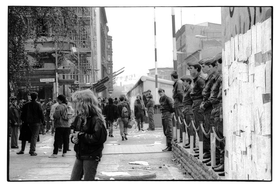 Eine Frau steht vor einre Mauer und Grenzsoldaten.