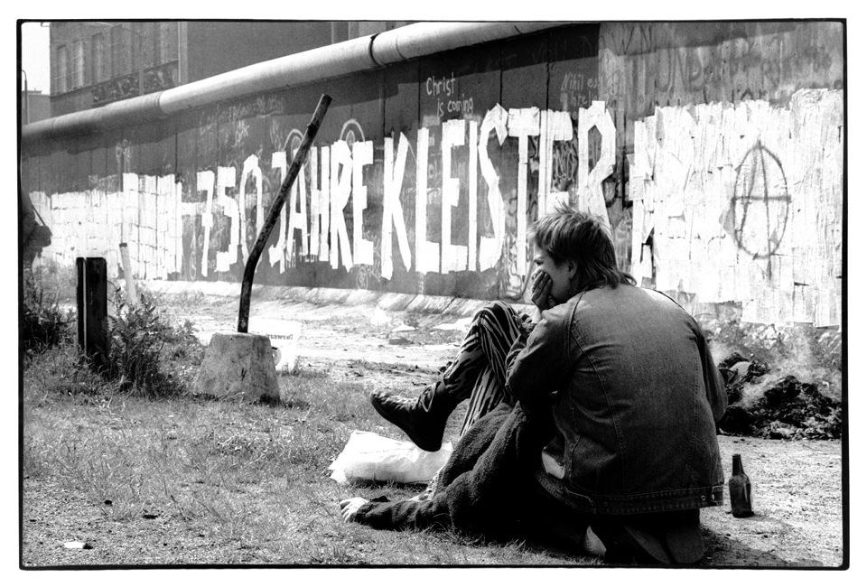 Ein Jugendlicher sitzt an einer Mauer.