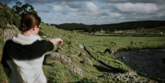 Eine Frau zeigt in ein grünes Tal, in dem Pferde auf einer Wiese weiden.