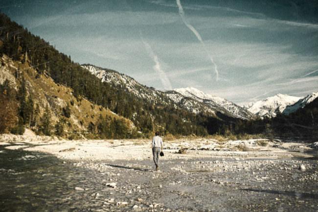 Ein Mann in einem flachen Tal umgeben von hohen Bergen.