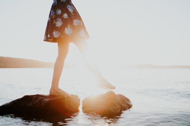 Die Beine einer Frau, die über Steine im Wasser balanciert.