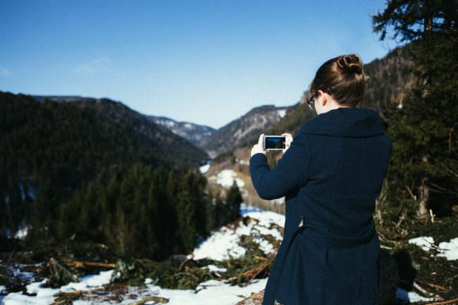 Eine Frau nimmt die Aussicht in ein Tal zwischen Bergen mit ihrem Handy auf.