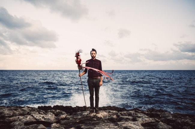 Ein Mann steht vor dem offenen Meer, das hinter ihm hochspritzt.