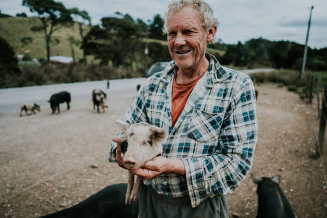 Ein Mann hält ein Schweinchen in den Händen.