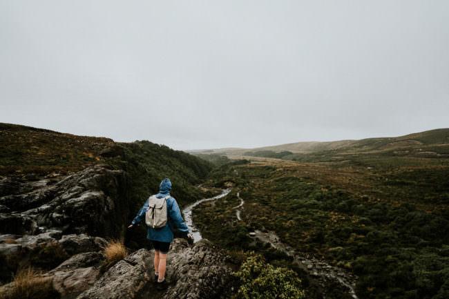 Ein Mensch in Regenjacke und mit Rucksack auf dem Rücken vor einer weiten, wilden Landschaft.