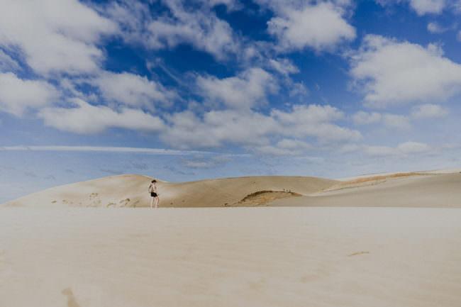 Eine Frau vor einer Dünenlandschaft unter blauem Himmel.