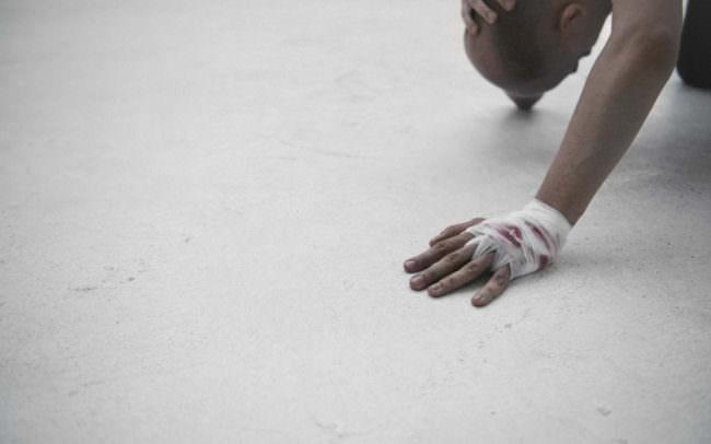 Ein Mensch mit blutigen Handschuh.