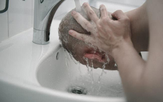 Ein Mann wäscht sich den Kopf.