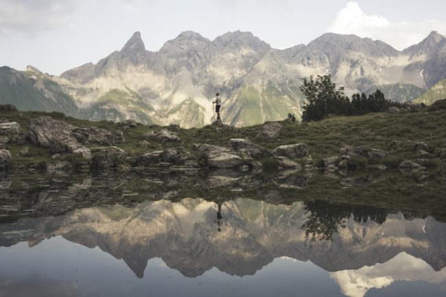 Ein Wanderer spiegelt sich in einem See