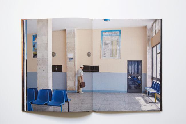 Aufnahme des aufgeschlagenen Buches mit doppelseitiger Abbildung, auf der ein Mann in einer leeren Bahnhofshalle zu sehen ist