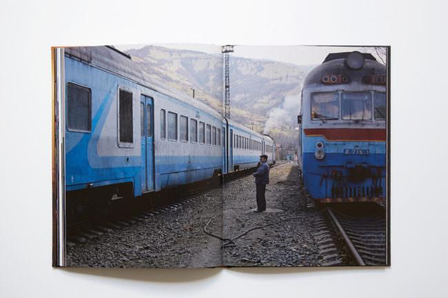 Aufnahme des aufgeschlagenen Buches mit doppelseitiger Abbildung, auf der ein Mann zu sehen ist, der zwischen zwei Zügen im Gleisbett steht