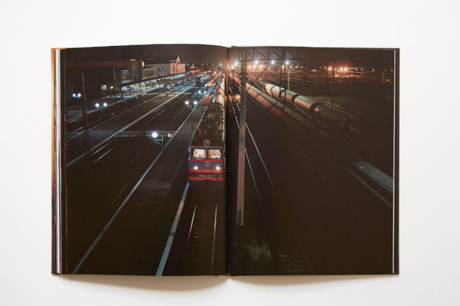 Aufnahme des aufgeschlagenen Buches mit doppelseitiger Abbildung eines nächtlichen Bahnhofs mit einfahrendem Zug