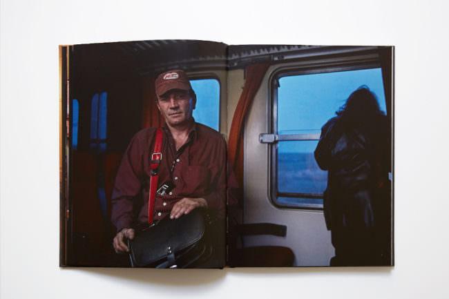 Aufnahme des aufgeschlagenen Buches mit doppelseitiger Abbildung eines Mann mit einer schwarzen Lederjacke im Vordergrund und einer langhaarigen Person im Hintergrund, die aus dem geöffneten Zugfenster schaut