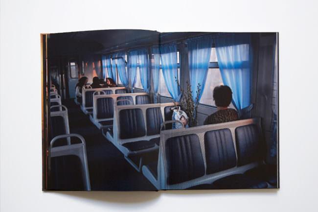 Aufnahme des aufgeschlagenen Buches mit doppelseitiger Abbildung einer Innenaufnahme aus dem Zug mit einer von hinten abgebildeten Frau im Vordergrund und drei Frauen mit Kopftüchern im Hintergrund