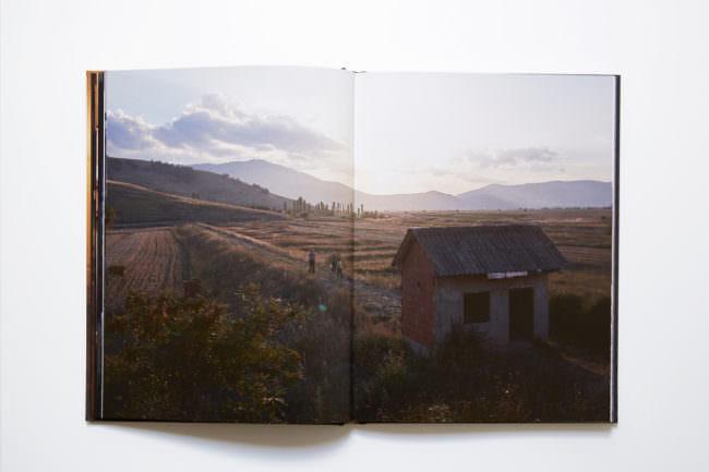 Aufnahme des aufgeschlagenen Buches mit doppelseitiger Abbildung, auf der eine Landschaftsaufnahme von einem Berg im Hintergrund und einem Haus im Vordergrund sowie drei Menschen auf einer Landstraße zu sehen ist