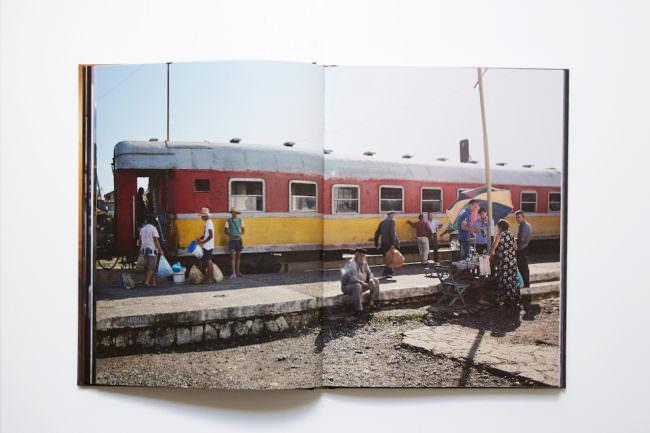 Aufnahme des aufgeschlagenen Buches mit doppelseitiger Abbildung, auf der eine Menschenmenge an einem Bahnsteig zu sehen ist