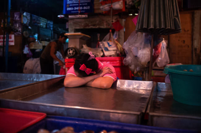 EIn Mädchen mit einer Schleife im Haar schläft mit dem Kopf auf einer Theke abgelegt