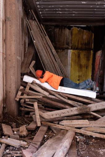 Ein Bauarbeiter schläft auf einem Haufen Holz