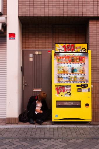 Ein Mensch schläft neben einem Snackautomaten