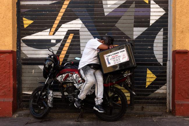 Ein Mann auf einem Moped schläft mit dem Kopf auf einer Styroporbox abgelegt