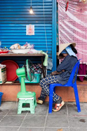 EineFrau mit einem großen Bambushut sitzt vor einem Ventilator auf einem Stuhl