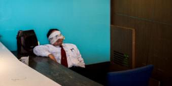 Ein Mann döst an eine Wand angelehnt, seine Augen mit einem Tuch verdeckt, darüber seine Brille
