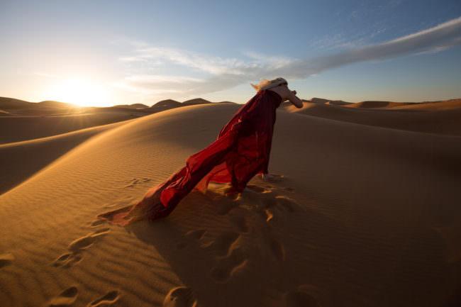 Frau in der Wüste mit rotem Kleid