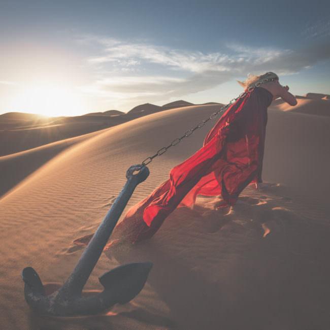 Frau schleppt einen Anker durch die Wüste
