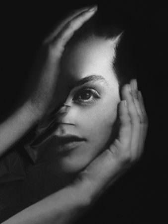 Bild eines Frauenkopfes in schwarz weiß welcher von 2 Händen gehalten und scheinbar verzogen wird.
