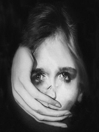 Portrait einer Frau in schwarz weiß welche eine Hand vor dem Mund hat.