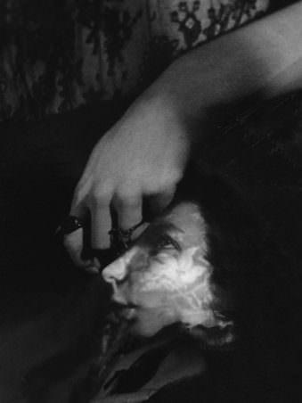 Seitenansicht eines Gesichts welches wie unter Wasser verschwommen scheint und scheinbar von einer Hand gehalten wird.