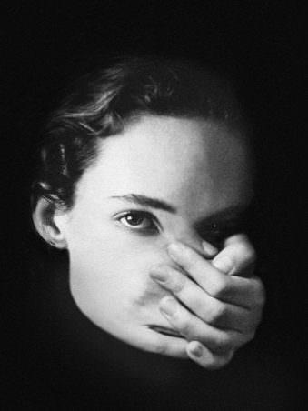 Portrait einer Frau mit Hand vor dem Mund
