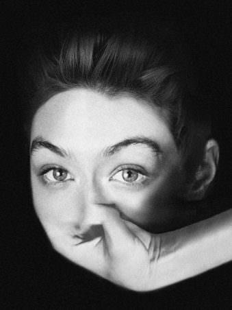 Portrait einer Frau in schwarz weiß die keinen Mund hat sondern eine Hand welche mit dem Gesicht verschmilzt.