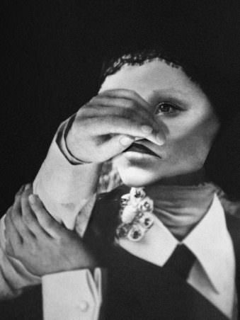 Portrait einer Frau in schwarz weiß der eine Hand vor das Gesicht gehalten wird.