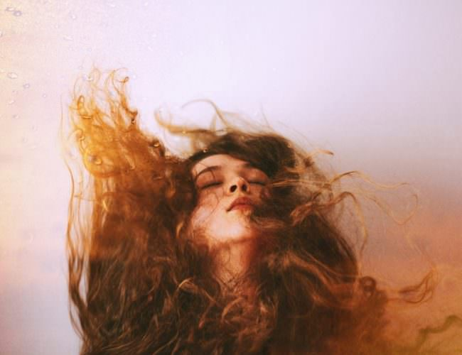 Portrait einer jungen Frau mit fliegenden langen Haaren.