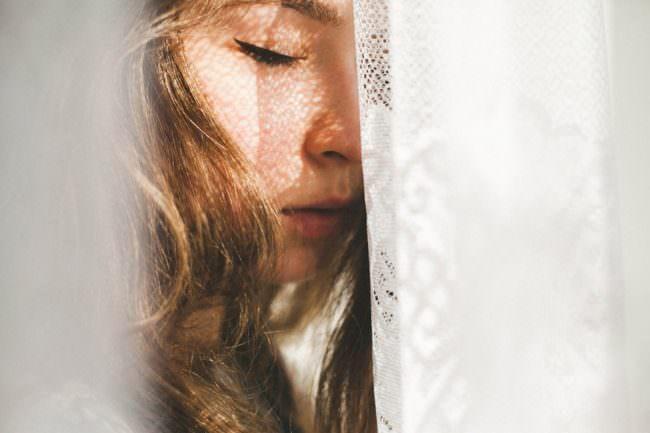 Portrait einer jungen Frau halb von einer Gardine verdeckt.