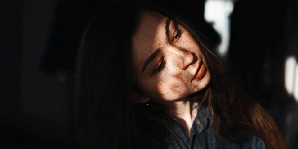 Portrait einer jungen Frau mit Lichtspiel im Dunkeln.