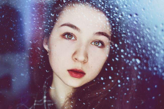 Portrait einer jungen Frau durch eine Scheibe mit Wassertropfen.