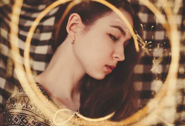 Portrait einer jungen Frau mit Lichtspuren einer Wunderkerze.