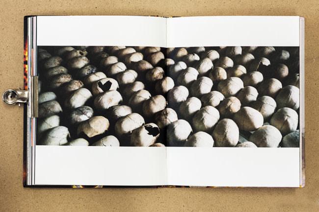 Aufgeschlagenes Buch mit Bild von aufgereihten Schädeln